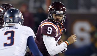 Virginia Tech quarterback Brenden Motley (9) tries to make the turn as Virginia safety Quin Blanding (3) closes in during the first half of an NCAA college football game in Blacksburg, Va., Friday, Nov. 28, 2014. (AP Photo/Steve Helber)