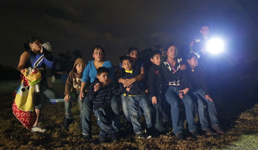 A group of immigrants from Honduras and El Salvador who crossed the U.S.-Mexico border illegally are stopped in Granjeno, Texas, on June 25, 2014. (Associated Press) ** FIL E**