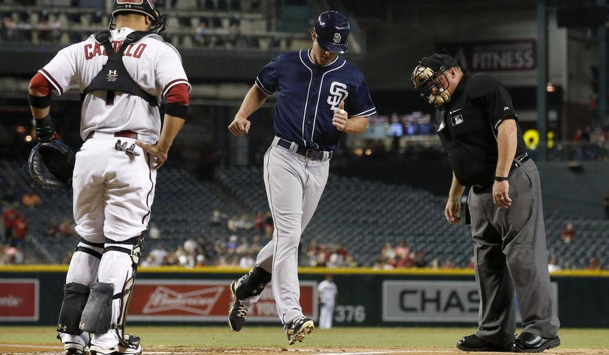 San Diego Padres' Wil Myers, middle, crosses home plate after hitting a home run as Arizona Diamondbacks' Welington Castillo, left, and umpire Bruce Dreckman, right, watch during the first inning of a baseball game, Monday, Sept. 14, 2015, in Phoenix. (AP Photo/Ross D. Franklin)