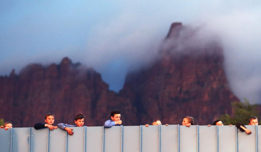 Residents of Hildale, Utah and Colorado City, Ariz.,  watch as work goes on to clean debris off of a bridge area after a flash flood on Tuesday, Sept. 15, 2015 in Colorado City, Ariz.  A wall of water swept away vehicles in the Utah-Arizona border town Monday, killing several people.  (Scott G Winterton/The Deseret News via AP)  SALT LAKE TRIBUNE OUT; MAGS OUT; MANDATORY CREDIT