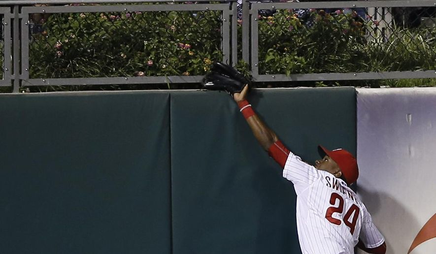 Philadelphia Phillies left fielder Darnell Sweeney cannot reach a two-run home run by Washington Nationals' Bryce Harper during the eighth inning of a baseball game, Tuesday, Sept. 15, 2015, in Philadelphia. Washington won 4-0. (AP Photo/Matt Slocum)