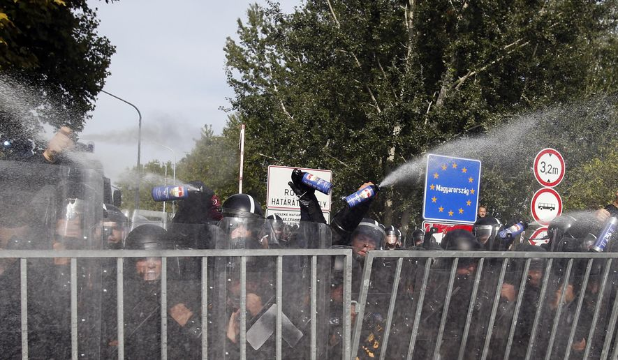"""Hungarian police use pepper spray at the """"Horgos 2"""" border crossing into Hungary, near Horgos, Serbia, Wednesday, Sept. 16, 2015. Small groups of migrants continued to sneak into Hungary on Wednesday, a day after the country sealed its border with Serbia and began arresting people trying to breach the razor-wire barrier, while a first group arrived in Croatia seeking another way into the European Union. (AP Photo/Darko Vojinovic)"""