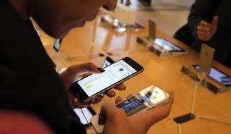 In this Sept. 19, 2014, file photo, a customer checks out the new iPhone 6 at an Apple store in Paris. (AP Photo/Christophe Ena, File)