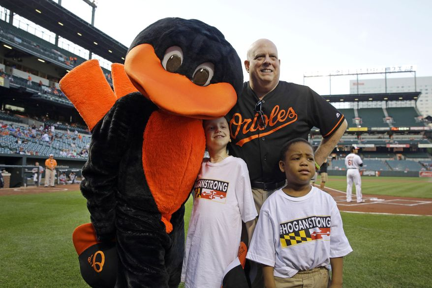 Maryland Gov. Larry Hogan, top right, poses with children and the Baltimore Orioles mascot before a baseball game between the Orioles and the Boston Red Sox, Wednesday, Sept. 16, 2015, in Baltimore. Hogan, who is undergoing treatment for Non-Hodgkins Lymphoma, visited the ballpark to help the Orioles announce a $50,000 donation to the Leukemia and Lymphoma Society and Ronald McDonald House Charities in the fight against pediatric cancer. (AP Photo/Patrick Semansky)