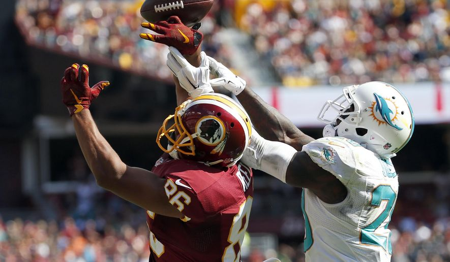 Miami Dolphins strong safety Reshad Jones (20) breaks up a pass intended for Washington Redskins tight end Jordan Reed (86) during the second half of an NFL football game, Sunday, Sept. 13, 2015, in Landover, Md. (AP Photo/Evan Vucci)