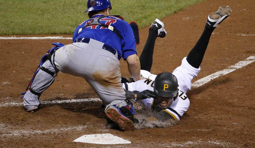 Chicago Cubs catcher Miguel Montero tags out Pittsburgh Pirates' Pedro Florimon during the eighth inning of a baseball game in Pittsburgh, Wednesday, Sept. 16, 2015. Florimon was going on contact on a ball hit to second baseman Starlin Castro by Josh Harrison. (AP Photo/Gene J. Puskar)