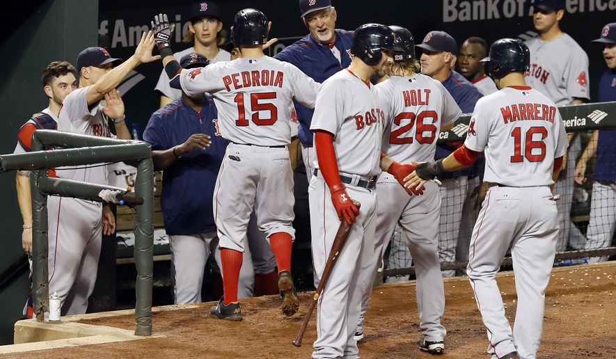 Boston Red Sox's Dustin Pedroia (15) high-fives teammates in the dugout after driving in Brock Holt (26) and Deven Marrero (16) on a three-run home run in the fourth inning of a baseball game against the Baltimore Orioles, Wednesday, Sept. 16, 2015, in Baltimore. (AP Photo/Patrick Semansky)