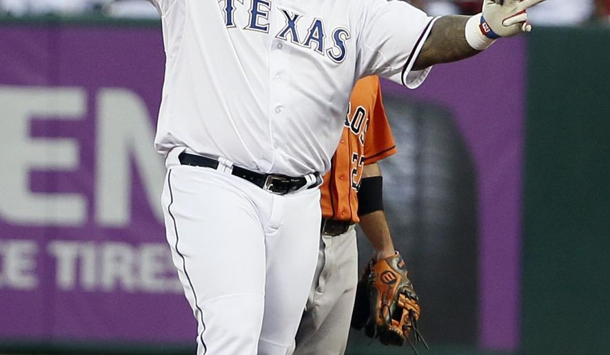 Texas Rangers' Prince Fielder gestures to the dugout after reaching second, following a single that scored Delino DeShields during the first inning of a baseball game against the Houston Astros on Tuesday, Sept. 15, 2015, in Arlington, Texas. Astros second baseman Jose Altuve is at rear. (AP Photo/Tony Gutierrez)
