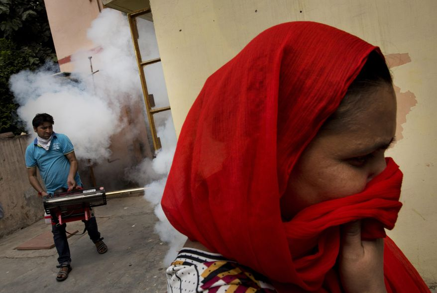 A woman covers her face as a municipal worker fumigates a residential area to prevent mosquitoes from breeding in New Delhi, India, Wednesday, Sept. 16, 2015. New Delhi has been hit by an outbreak of the mosquito-borne disease, dengue fever. Nearly 1,900 cases have been recorded in the city's hospitals.(AP Photo/Bernat Armangue)