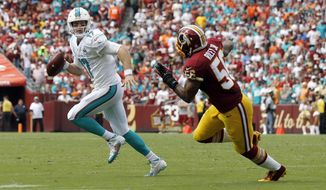 Miami Dolphins quarterback Ryan Tannehill (17) looks to pass as he is pursued by Washington Redskins inside linebacker Perry Riley (56) during the first half of an NFL football game Sunday, Sept. 13, 2015, in Landover, Md. Tannehill threw a touchdown pass on the play. (AP Photo/Patrick Semansky)