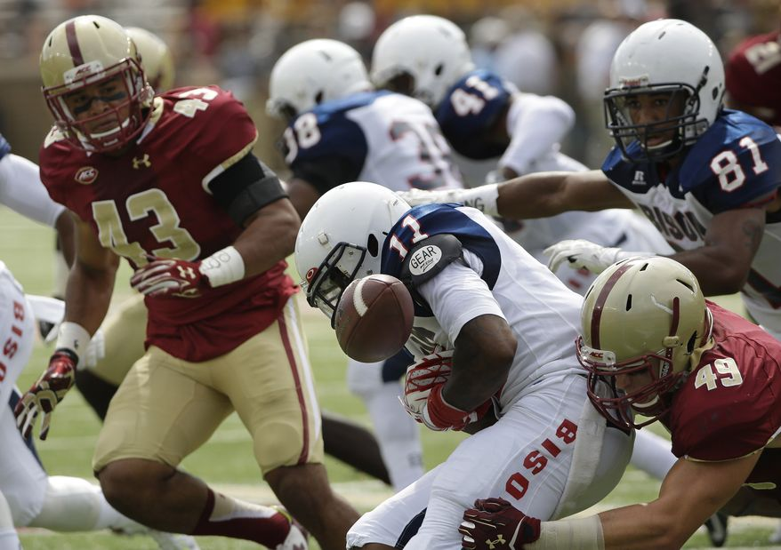 Howard defensive back Julian Blair (11) coughs up the ball as he is hit by Boston College tight end Cameron Croteau (49) during a first half kick return in their NCAA college football game Saturday, Sept. 12, 2015, in Boston. Boston College linebacker Sharrieff Grice (43) looks on as Boston College defeated Howard 76-0 in a game that had the third and fourth quarters shortened to 10 minutes each. (AP Photo/Stephan Savoia)