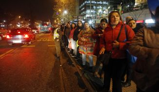 A police officer stands in the street to flag down buses for people to take home after an earthquake in Santiago, Chile on Wednesday. A powerful magnitude-8.3 earthquake hit off Chile's northern coast Wednesday night, causing buildings to sway in Santiago and other cities and sending people running into the streets. (Associated Press)