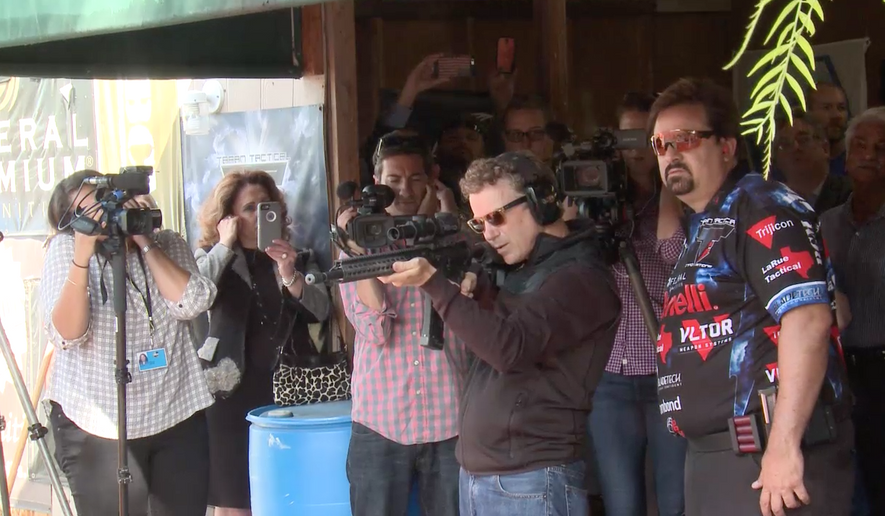 Rand Paul fires a gun in California into boxes holding the IRS tax code. Source: TellDC