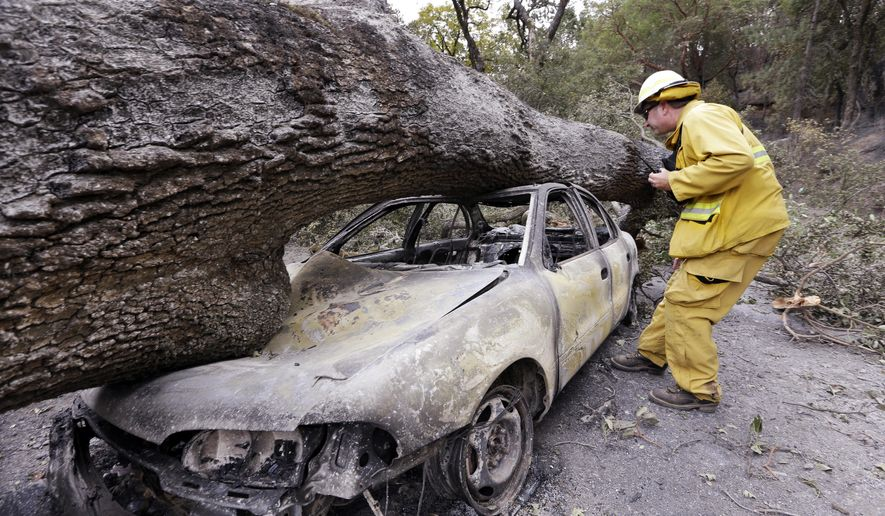 Firefighter Jeff Ohs looks into a burned out car that was also hit by a tree at the Harbin Hot Springs resort in a wildfire several days earlier, Tuesday, Sept. 15, 2015, near Middletown, Calif. The fire that sped through Middletown and other parts of rural Lake County, less than 100 miles north of San Francisco, has continued to burn since Saturday despite a massive firefighting effort. (AP Photo/Elaine Thompson)