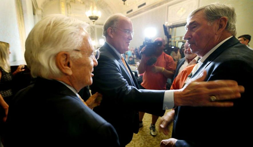 Interim athletic director Michael Perrin, center, greets former AD DeLoss Dodds after a press conference, Wednesday, Sept. 16, 2015, announcing Steve Patterson's replacement after his departure the day before. (Ricardo Brazziell /Austin American-Statesman via AP)  AUSTIN CHRONICLE OUT, COMMUNITY IMPACT OUT, INTERNET AND TV MUST CREDIT PHOTOGRAPHER AND STATESMAN.COM, MAGS OUT; MANDATORY CREDIT
