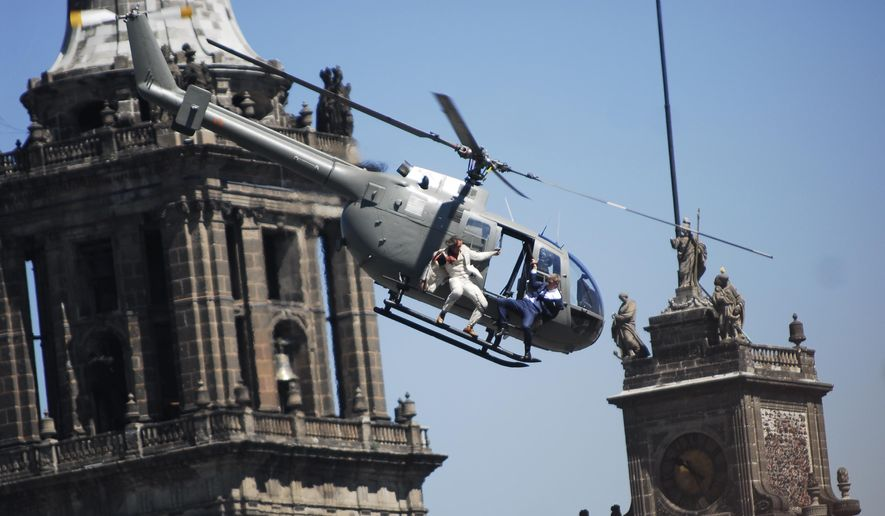 "In this Monday, March 30, 2015, file photo, stunt doubles perform an action scene aboard a helicopter above the Zocalo, Mexico City's main square, during the filming of ""Spectre,"" the latest of the James Bond 007 movies, in Mexico. (AP Photo/Sandra Stargardter, File)"