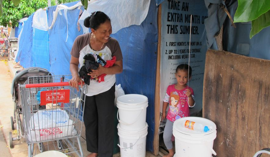 Kionina Kaneso, left, smiles at her granddaughter Keioleen Helly, right, plays with an antenna outside the structure where they live on a sidewalk on Wednesday, Sept. 16, 2015, in Honolulu. Kaneso is among the plaintiffs in a lawsuit the American Civil Liberties Union filed Wednesday against the city of Honolulu, claiming city officials deprived homeless people of food and other belongings during raids on encampments. (AP Photo/By Cathy Bussewitz)