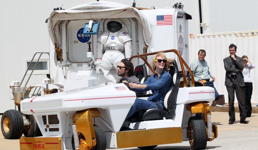 "Actress Mackenzie Davis and fellow ""The Martian"" cast member, Sebastian Stan, take a  Modular Robotic Vehicle for a 360 degree spin Tuesday Sept. 15, 2015, outside the Space Vehicle Mockup Facility at NASA's Johnson Space Center in Houston, Texas. (Jennifer Reynolds/The Galveston County Daily News via AP)"
