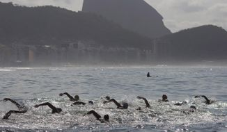"FILE - In this Aug. 22, 2015 file photo, backdropped by Sugar Loaf Mountain, athletes compete in the men's marathon swimming test event, ahead of the Rio 2016 Olympic Games, off Copacabana Beach, Rio de Janeiro, Brazil.  Swimming's world governing body FINA has strongly criticized the organizers of next year's Olympics in Rio de Janeiro over what it says are substandard facilities and ""disrespect"" for aquatic events.  (AP Photo/Leo Correa, File)"