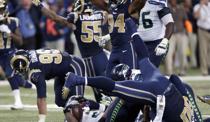 FILE - In this Sunday, Sept. 13, 2015 file photo, Seattle Seahawks running back Marshawn Lynch, bottom, lands on his back after being stopped on fourth down as St. Louis Rams players celebrate on the final play in overtime of an NFL football game in St. Louis. Seattle Seahawks coach Pete Carroll brushed aside comments made by Marshawn Lynch's mother Delisa Lynch in a Facebook post criticizing the organization and calling for offensive coordinator Darrell Bevell to be fired.  Her comments came after her son was stopped on a fourth-and-1 run play in overtime in the Seahawks' 34-31 loss in St. Louis on Sunday, Sept. 13, 2015. (AP Photo/Tom Gannam, File)