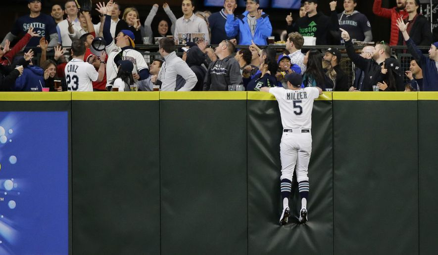 Fans along the center field wall join Seattle Mariners center fielder Brad Miller in looking for a home run hit by Los Angeles Angels' Mike Trout during the sixth inning of a baseball game, Tuesday, Sept. 15, 2015, in Seattle. (AP Photo/Ted S. Warren)