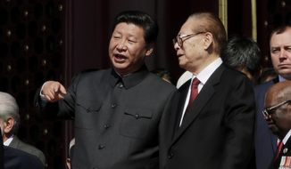 Chinese President Xi Jinping, left, talks with former Chinese President Jian Zemin during a parade commemorating the 70th anniversary of Japan's surrender during World War II held in front of Tiananmen Gate, in Beijing, Thursday, Sept. 3, 2015. (AP Photo/Ng Han Guan)