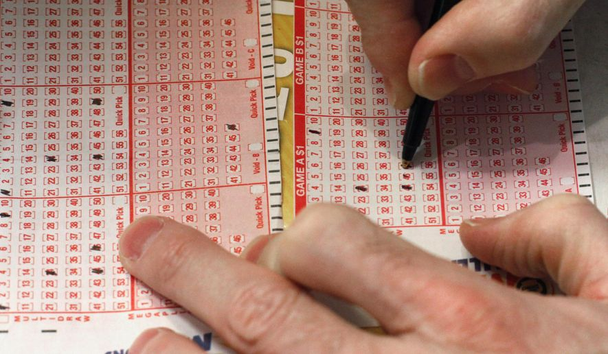 FILE - In this March 29, 2012 file photo, a customer fills out a lottery form for the Mega Millions drawing in Chicago. A new report from the Illinois Legislature has found that the Illinois Lottery lost money last year for the first time since 2009. The loss comes after the state hired a private manager to increase the lottery's sales and profits. (AP Photo/Charles Rex Arbogast, File)
