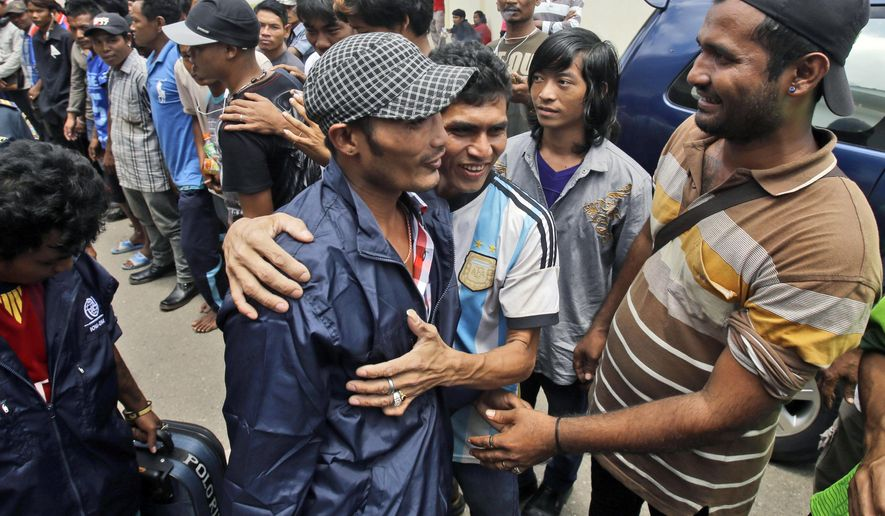In this Sept. 8, 2015 photo, a Burmese fisherman, center, is embraced by a friend as he leaves the port town of Ambon, Maluku province, Indonesia. More than 2,000 fishermen have been rescued this year from brutal conditions at sea, their freedom prompted by an Associated Press investigation into seafood brought to the U.S. from a slave island in eastern Indonesia. Dozens of Burmese men in the bustling port town of Ambon were the latest to go home, some more than a decade after being trafficked onto Thai trawlers.  (AP Photo/Achmad Ibrahim)
