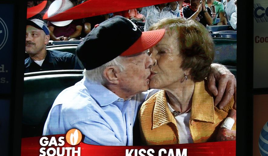 "Former President Jimmy Carter kisses his wife, Rosalynn, on the ""Kiss Cam"" during a baseball game between the Atlanta Braves and the Toronto Blue Jays on Thursday, Sept. 17, 2015, in Atlanta. Carter recently announced he has cancer. (AP Photo/John Bazemore)"