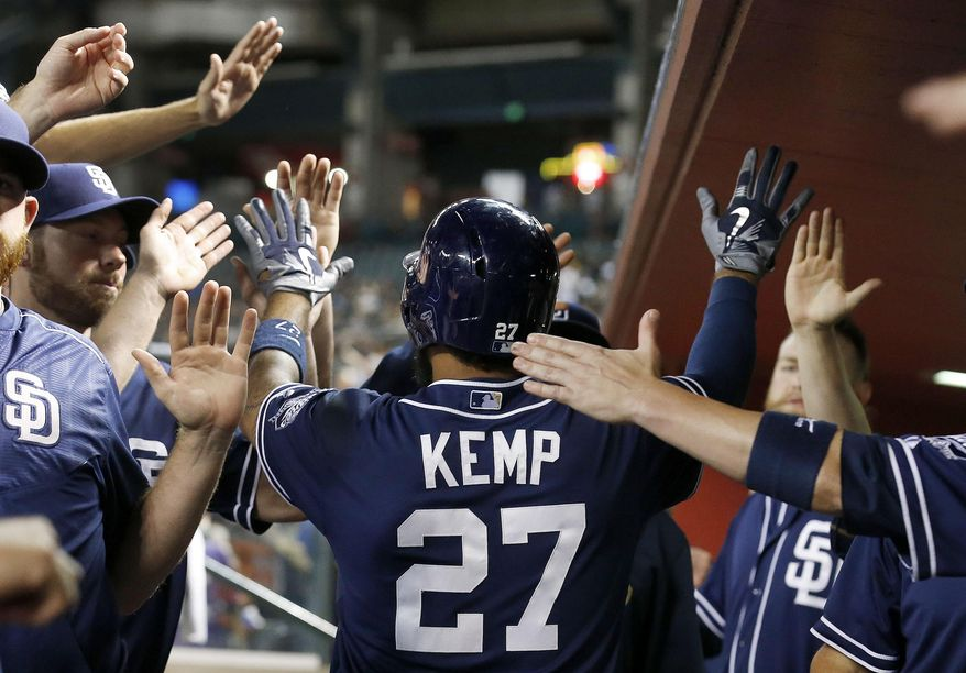 San Diego Padres' Matt Kemp gets high-fives from teammates in the dugout after his three-run home run against the Arizona Diamondbacks during the fifth inning of a baseball game Wednesday, Sept. 16, 2015, in Phoenix. (AP Photo/Ross D. Franklin)