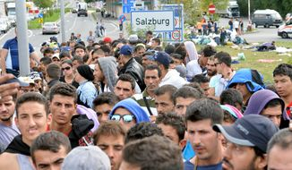 Refugees wait on a bridge after police stopped them at the border between Austria and Germany in Salzburg, Austria, Thursday, Sept. 17, 2015. (AP Photo/Kerstin Joensson)
