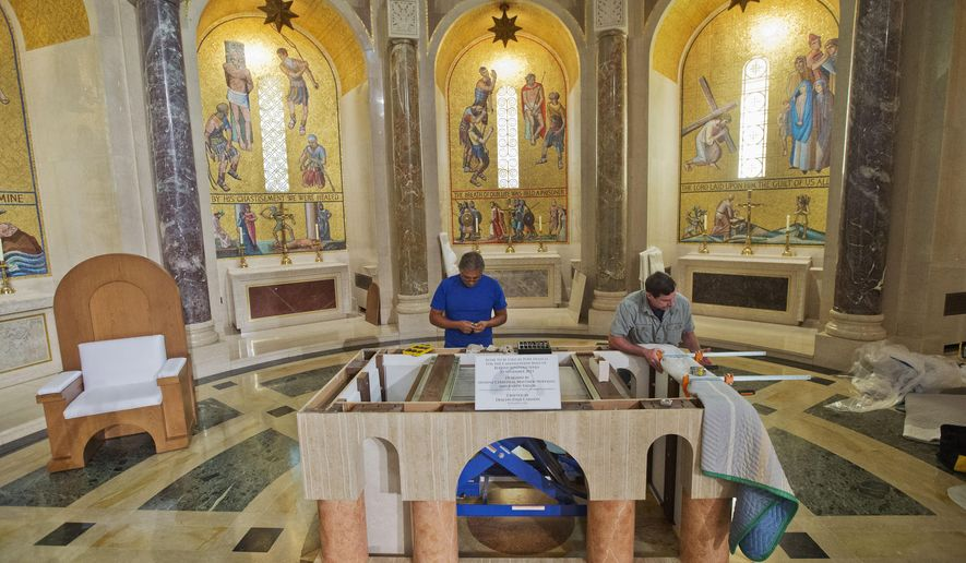 Deacon David Cahoon, right, from the Archdiocese of Washington and professional carpenter, and head carpenter Carlos Hernandez, left, continue to work on the altar that Pope Francis will use during his Mass next week, inside the Basilica of the National Shrine of the Immaculate Conception in Washington, Thursday, Sept. 17, 2015. (AP Photo/Pablo Martinez Monsivais)