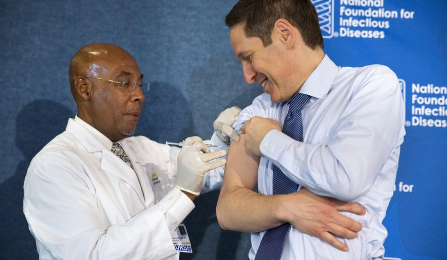 Centers for Disease Control and Prevention Director Dr. Tom Frieden, right, receives a flu shot from nurse B.K. Morris during an event about the flu vaccine, Thursday, Sept. 17, 2015, at the National Press Club in Washington. It's time for flu shots again, and health officials expect to avoid a repeat of the misery last winter, when immunizations weren't a good match for a nasty surprise strain.  (AP Photo/Jacquelyn Martin)