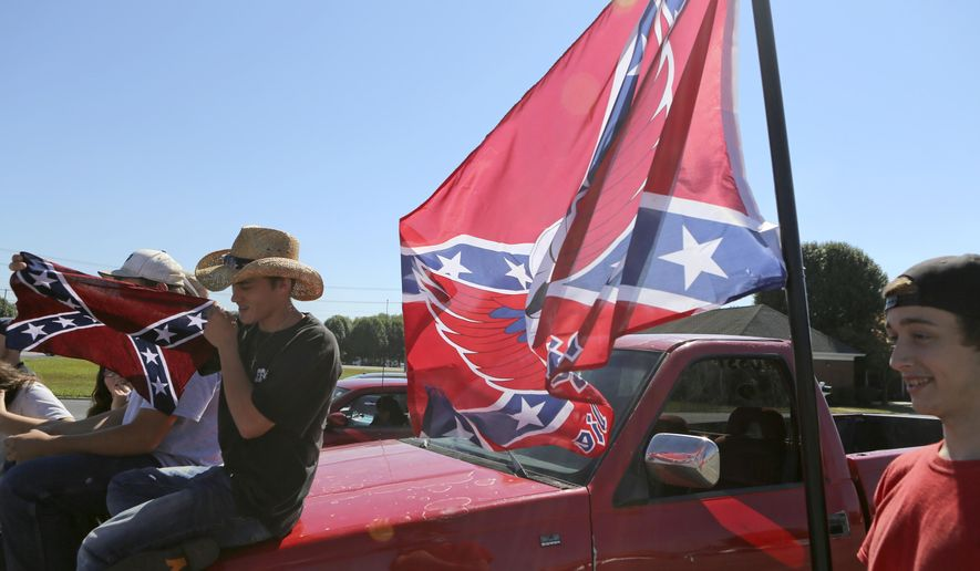 Christiansburg High School student Sam Sheppard, left, displays a Confederate flag while fellow student Andrew Love displays another flag in a shopping center parking lot after being suspended from school in Christiansburg, Va., Thursday, Sept. 17, 2015. Roughly 20 students at the Virginia high school received a one-day suspension for wearing clothing displaying the Confederate flag. A rally was also organized outside the school Thursday to protest a new school policy banning vehicles with Confederate symbols from its parking lot. (Matt Gentry /The Roanoke Times via AP) LOCAL TELEVISION OUT; SALEM TIMES REGISTER OUT; FINCASTLE HERALD OUT;  CHRISTIANBURG NEWS MESSENGER OUT; RADFORD NEWS JOURNAL OUT; ROANOKE STAR SENTINEL OUT; MANDATORY CREDIT