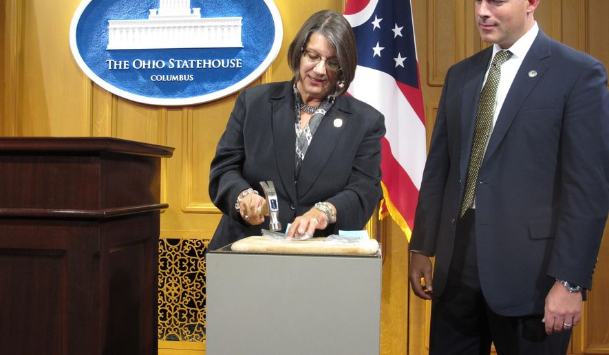 State Rep. Nickie Antonio, left, a Lakewood Democrat, demonstrates the power of tamper resistant pain pills by unsuccessfully trying to pulverize them with a hammer, while Rep. Robert Sprague, a Findlay Republican, awaits his turn, on Thursday, Sept. 17, 2015, in Columbus, Ohio. The lawmakers are sponsoring a bill to require insurance companies to cover the tamper resistant drugs, which are more expensive but harder for addicts to abuse. (AP Photo/Andrew Welsh-Huggins)