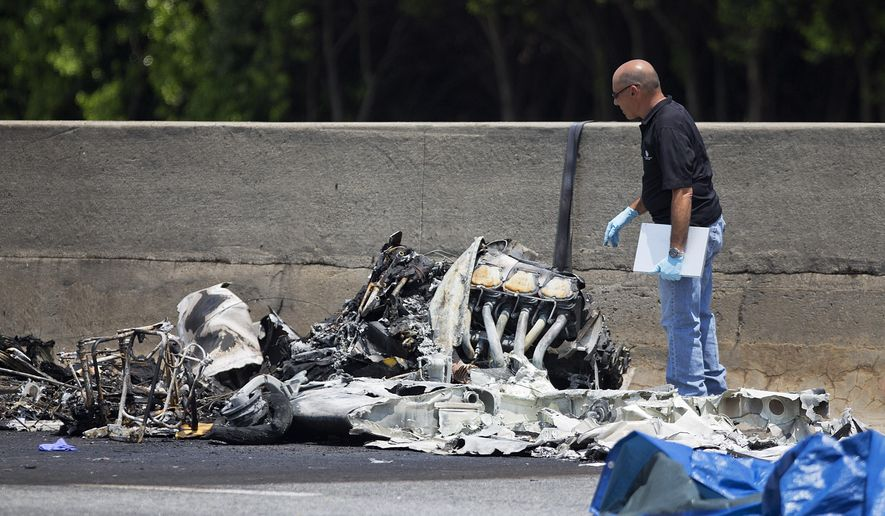 FILE - In this May 8, 2015, file photo, an investigator looks at the wreckage of a plane that crashed on Interstate 285 in Doraville, Ga. The Federal Aviation Administration released the five-minute audio Thursday, Sept. 17, of pilot Greg Byrd III's pre-flight routine before he said he was struggling to gain altitude and crashed. (AP Photo/David Goldman, File)