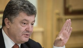 In this photo made Wednesday, Sept. 16, 2015, Ukrainian President Petro Poroshenko speaks with EU officials in Kiev, Ukraine. Poroshenko on Wednesday signed a decree, banning entry to Ukraine to nearly 400 individuals, dozens of reporters including three Moscow-based BBC journalists. The decree said that all the journalists on the list were an unspecified security threat. (AP Photo/ Mykhailo Markiv, Pool)