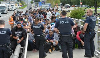 Refugees sit on a bridge after police stopped them at the border between Austria and Germany in Salzburg, Austria, Thursday, Sept. 17, 2015. (AP Photo/Kerstin Joensson)