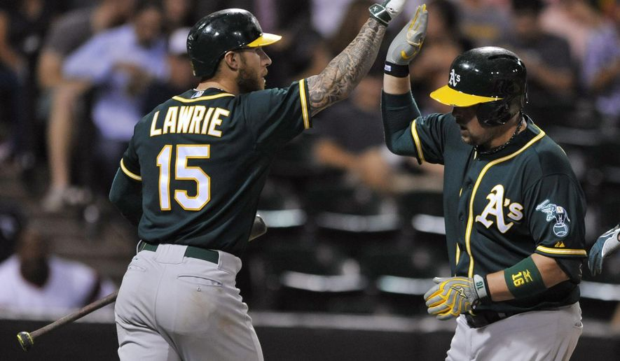 Oakland Athletics' Billy Butler, right, celebrates with teammate Brett Lawrie at home plate after hitting a two-run home run during the sixth inning of a baseball game against the Chicago White Sox on Wednesday, Sept. 16, 2015, in Chicago. (AP Photo/Paul Beaty)