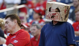 A fan wears a bag over his head before a baseball game between the Washington Nationals and the New York Mets at Nationals Park, Wednesday, Sept. 9, 2015, in Washington. (AP Photo/Alex Brandon)