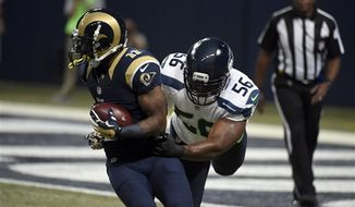 St. Louis Rams wide receiver Tavon Austin (11) catches a pass as Seattle Seahawks defensive end Cliff Avril defends during the first quarter of an NFL football game Sunday, Sept. 13, 2015, in St. Louis. (AP Photo/L.G. Patterson)