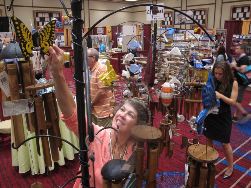 Diane Anderson arranges wind chimes her garden and gift company was showing at a trade show Thursday Sept. 17, 2015 at Harrah's Resort Atlantic City in Atlantic City, N.J. The new $126 million conference center is part of an effort to expand Atlantic City's appeal beyond gambling and attract new business. (AP Photo/Wayne Parry)
