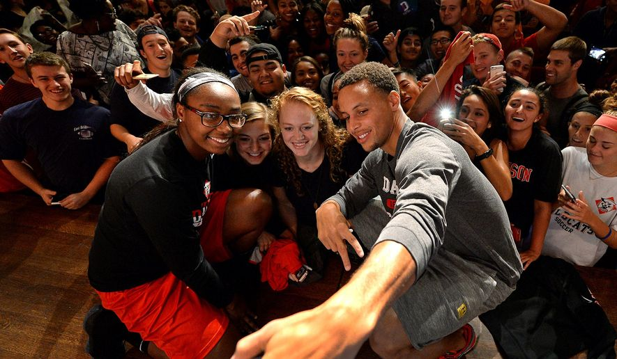 Davidson College women's basketball players Kyla Roland, left, Mackenzie Latt, second from left, and Hannah Early, second from right, pose for a selfie with former Davidson All-American and NBA All Star Stephen Curry, after Curry finished a question and answer session at the Belk Performing Center, Thursday, Sept. 17, 2015, in Davidson, N.C. Curry, of the Golden State Warriors, made a surprise visit to his alma mater, bringing the Larry O'Brien NBA championship trophy along with him to show off. (Jeff Siner/The Charlotte Observer via AP) MAGS OUT; TV OUT; MANDATORY CREDIT