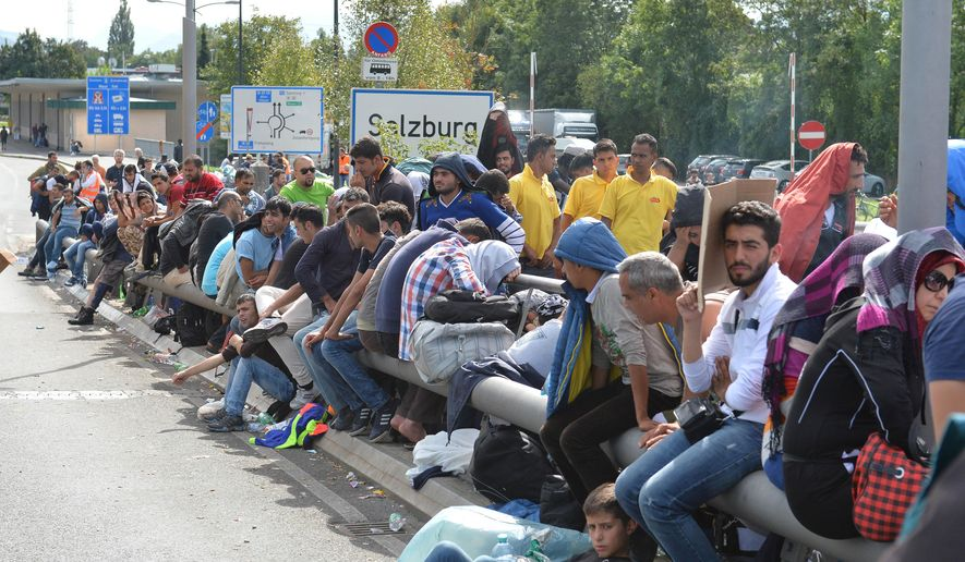 Refugees rest on the roadside after police stopped them near the border between Austria and Germany, in Salzburg, Austria, Thursday, Sept. 17, 2015. (AP Photo/Kerstin Joensson)