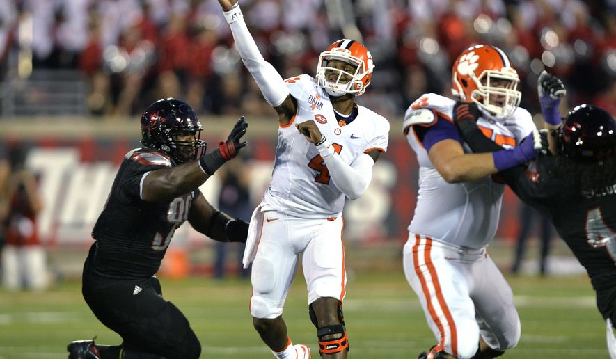 Clemson quarterback D3eshaun Watson (4) throws a pass under pressure form Louisville's Sheldon Rankins (98) during the first half of an NCAA college football game in Louisville, Ky., Thursday, Sept. 17, 2015. (AP Photo/Timothy D. Easley)