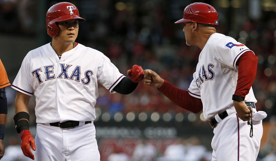 Texas Rangers' Shin-Soo Choo, left, bumps fists with first base coach Hector Ortiz after hitting a single off of Houston Astros starting pitcher Lance McCullers during the first inning of a baseball game Thursday, Sept. 17, 2015, in Arlington, Texas. (AP Photo/Tony Gutierrez)