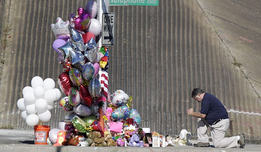 A man prays the site of an accident that involved a school Wednesday, Sept. 16, 2015, in Houston. The bus plunged off a highway overpass in Houston after being hit by a car Tuesday, injuring multiple students and killing two, police and school officials said. (James Nielsen/Houston Chronicle via AP) MANDATORY CREDIT