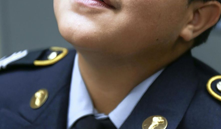 In this photo taken on Thursday, Sept. 10, 2015, J.H. Rose ROTC Staff Sergeant Laith Hamed get assistance with his pins after receiving his new uniform in the ROTC Building at J.H. Rose High School in Greenville, N.C. (Aileen Devlin /The Daily Reflector via AP) MANDATORY CREDIT