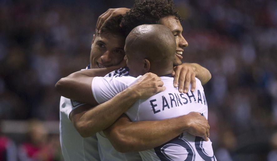 Vancouver Whitecaps' Nicolas Mezquida, left,, Kianz Froese, back right, and Robert Earnshaw celebrate Froese's goal against C.D. Olimpia during the first half of a CONCACAF Champions League soccer game in Vancouver, British Columbia, on Wednesday, Sept. 16, 2015. (Darryl Dyck/The Canadian Press via AP)