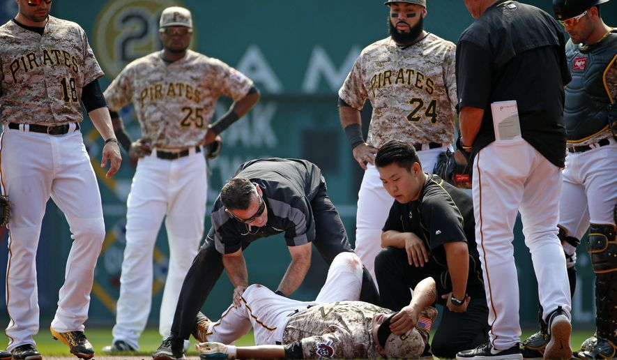 Pittsburgh Pirates' Jung Ho Kang, bottom center, is tended to by a team trainer after injuring his left leg turning a double play in the first inning of a baseball game against the Chicago Cubs in Pittsburgh, Thursday, Sept. 17, 2015. Kang left the game. (AP Photo/Gene J. Puskar)